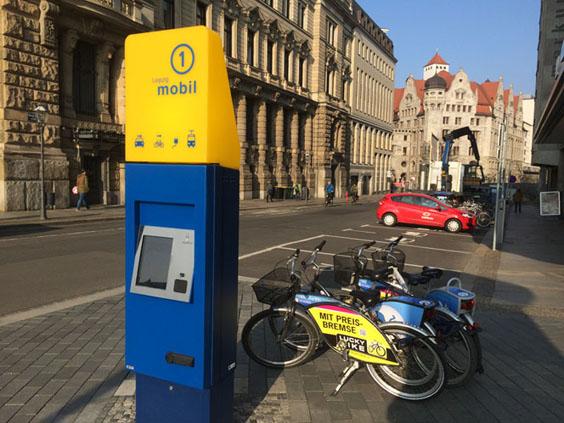 """Mobilitätsstation am Wilhelm-Leuschner-Platz in Leipzig mit Fahrrad- und PKW-Leihmöglichkeit sowie Ladepoller vor dem """"teilAuto"""" hinten rechts."""